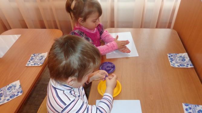 2 детей раскатывают пластилин в ладонях
