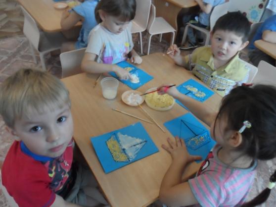 4 детей сидят за столом и на синем фоне делают мозаичную аппликацию
