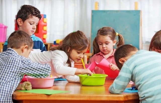 Дети сидят за столом, рисуют, макая кисточки в тазик