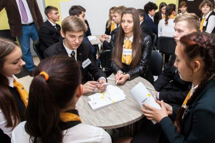 Дети-старшеклассники сидят за круглым столом