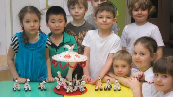 Дети вокруг стола с дымковскими пластилиновыми лошадками