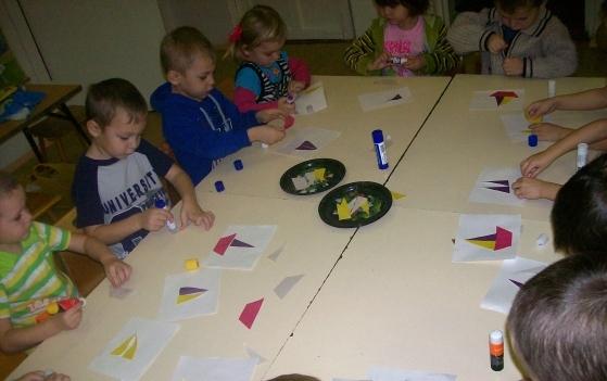 Дети за длинным столом клеят треугольники лодки на подложку