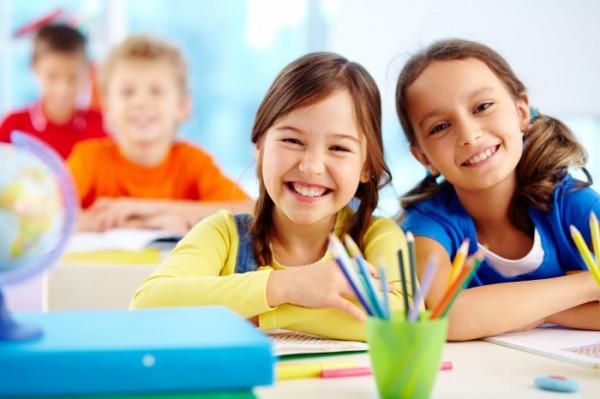 Дети за столом с ручками в стакане, на первом плане две девочки, на заднем — два мальчика