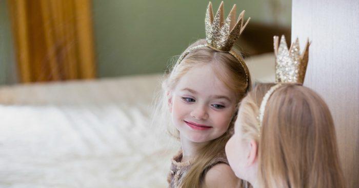 девочка в короне смотрит в зеркало