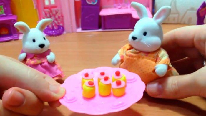Кексы на тарелке перед двумя зайцами