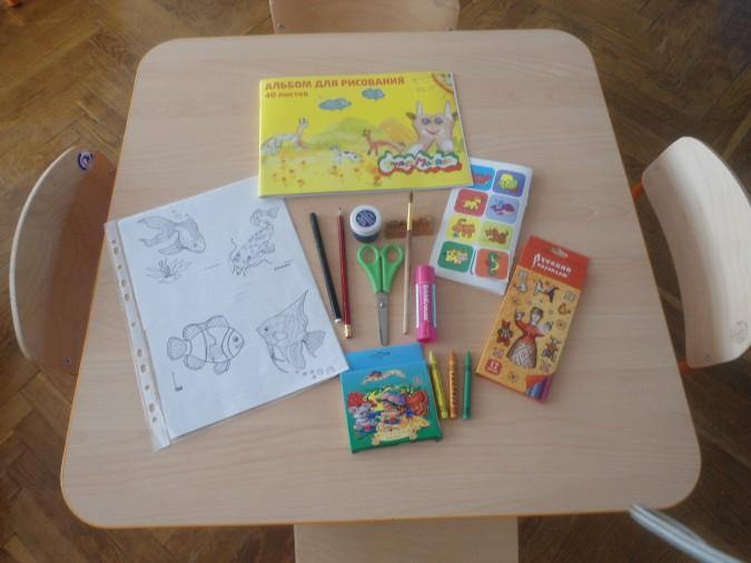 Кисточка, карандаши, альбом для рисования, картинки с рыбками на столике