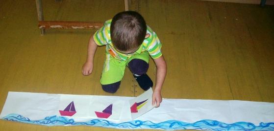 Мальчик клеит лодочку на длинную «речку»