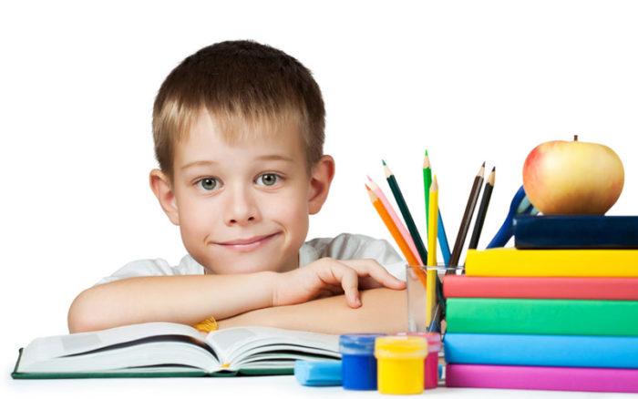 Мальчик перед раскрытой книгой и карандашами в стакане