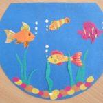 Приклеенные рыбки из цветной бумаги на круглом синем аквариуме