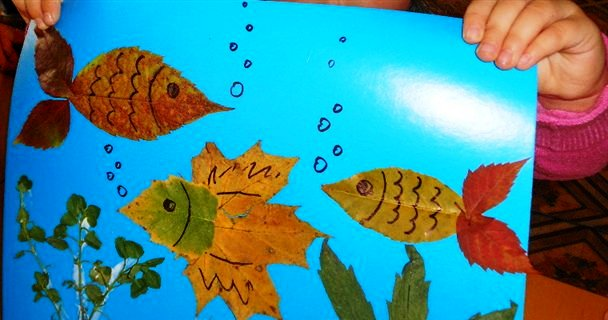Рыбки из листочков на синем картоне, аппликация держит малыш