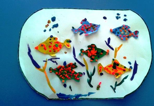 Рыбки с пластилиновыми чешуйками на белом фоне аквариума