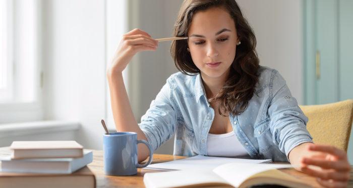 Девушка за столом с карандашом в руке