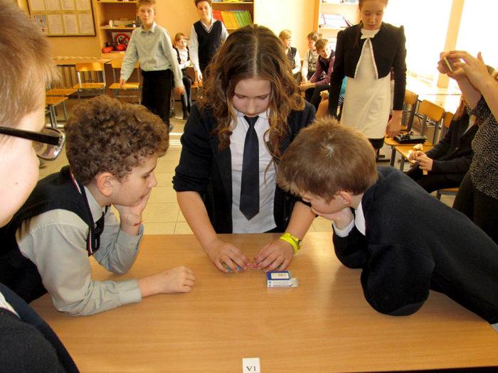 Трое детей работают за столом в группе