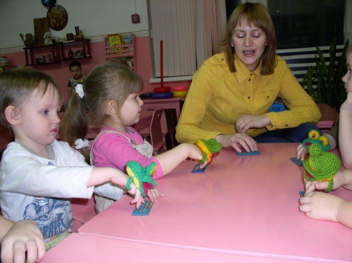 Воспитательница и 3 детей выполняют пальчиковую гимнастику