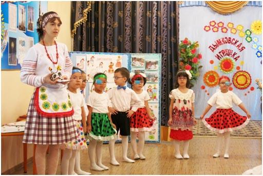 Воспитательница и дети в костюмах вятского края, на заднике буквы «дымковская игрушка»