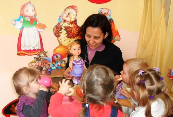 Воспитательница общается с детьми, держит в руках куклу