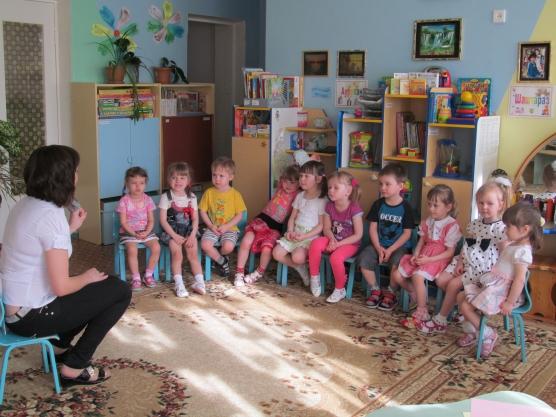 Воспитательница рассказывает что-то детям, сидящим полукругом напротив неё