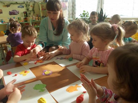 Воспитательница вместе с детьми за столом делает рыбок