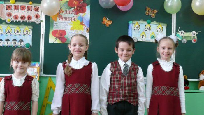3 девочки и мальчик в форме вишнёвого цвета стоят у доски