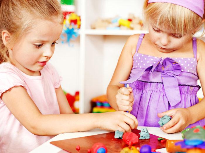 Две девочки лепят из пластилина