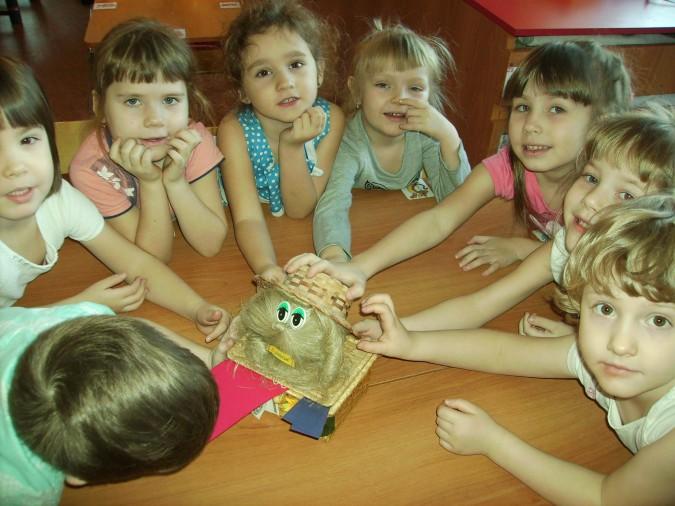 Дети трогают соломенную шапку на домовёнке