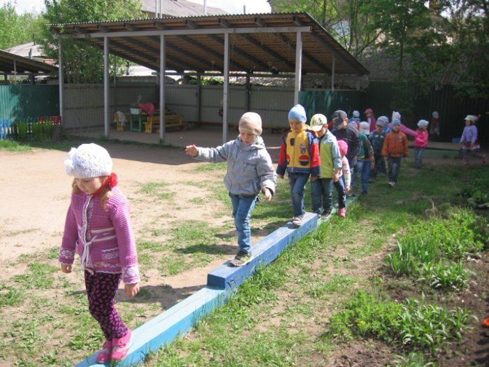 Дети в саду идут по деревянным брускам