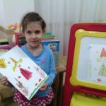 Девочка держит рисунок гнома в красной рубашке и жёлтом колпачке