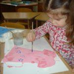 Девочка раскрашивает розовое платье методом тычка
