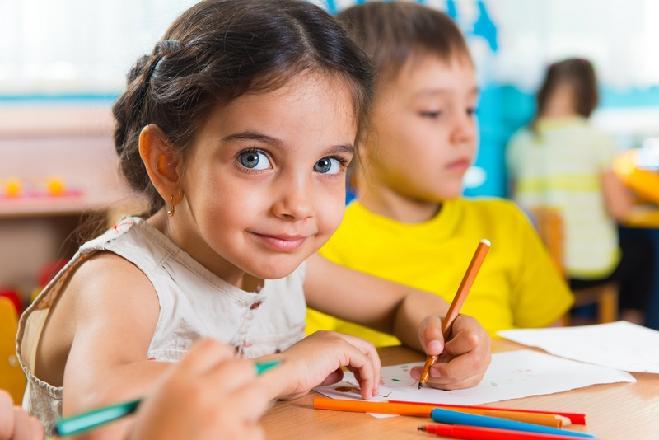 Девочка с большими глазами сидит за столом, держит фломастер