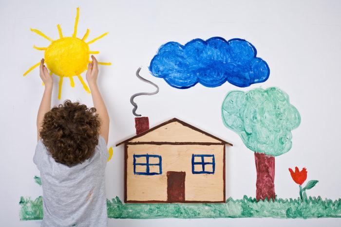 ребёнок на фоне большого рисунка с домиком
