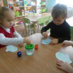 Мальчик и девочка раскрашивают варежки ватной палочкой