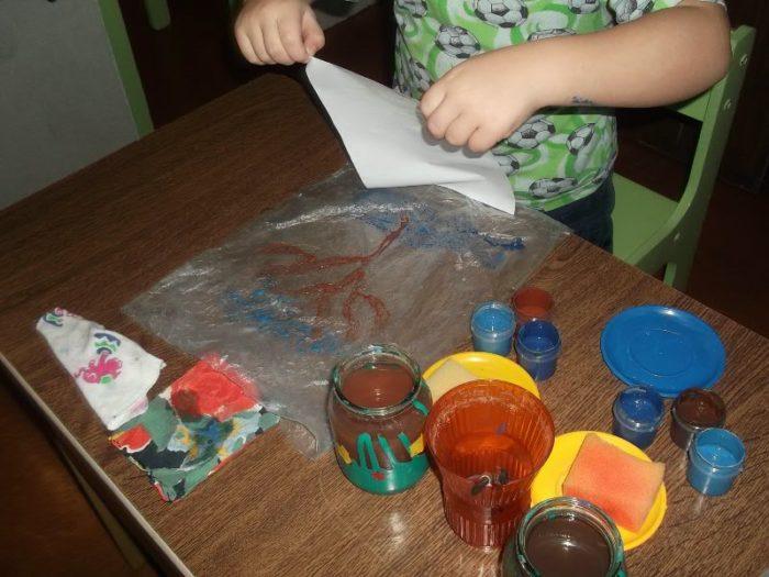 Ребёнок в детском саду делает работу в технике монотипии