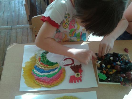 ребёнок выполняет мозаичную аппликацию пластилином