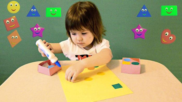Ребёнок клеит фигурки на лист