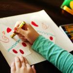 Рука ребёнка с голубой кофте раскрашивает шаблоны варежек восковыми мелками
