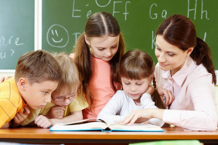 Учительница сидит с 4 детьми над книжками