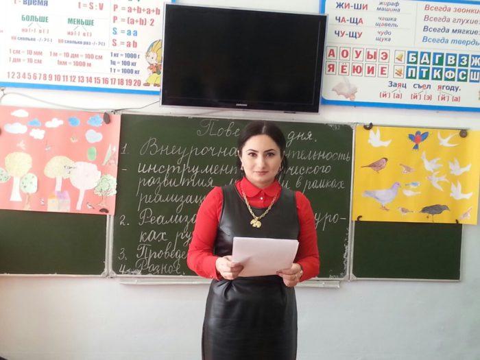 Учительница в красной блузке и кожаном сарафане читает доклад