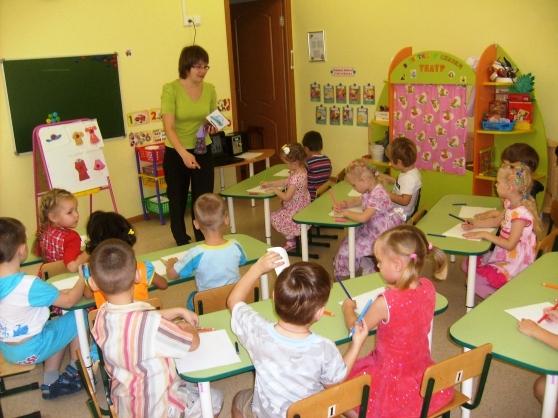 Воспитательница показывает детям средней группы картинку с шапочкой