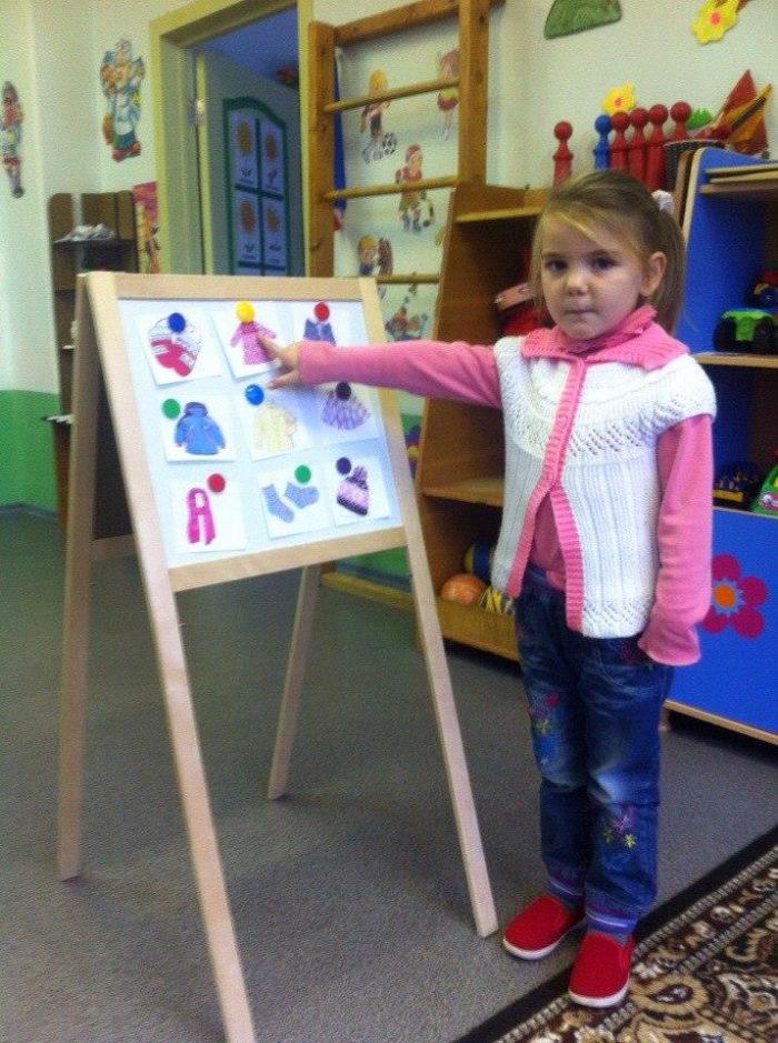 Девочка стоит возле доски, где закреплены карточки с изображениями предметов одежды