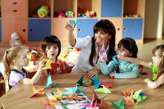 Дети и воспитатель делают разноцветных птичек в технике оригами