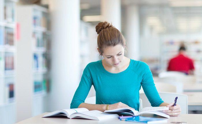 Женщина читает книгу в библиотеке