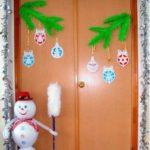 Дверь, украшенная искусственными еловыми ветками и бумажными шарами