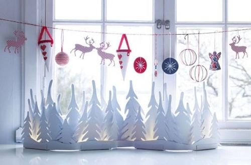 Ёлки, вырезанные из белой бумаги и гирлянда из бумажных игрушек