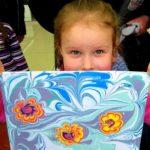 Девочка держит рисунок «Цветы распустились»