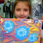 Девочка держит рисунок с голубыми цветами