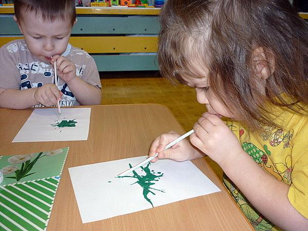 Мальчик и девочка раздувают краску через соломинки
