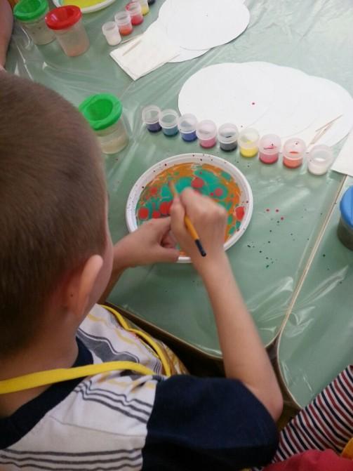 Ребёнок рисует узоры на воде, налитой в круглую пластиковую тарелку