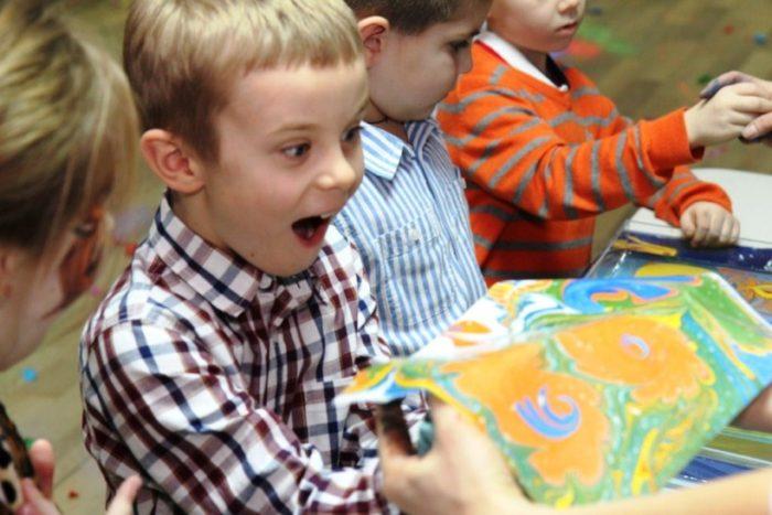 Мальчик удивлённо смотрит на рисунок, выполненный в технике эбру