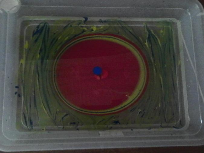 В центре основы нанесены друг на друга капли разного цвета, образующие круги