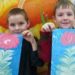 Два мальчика держат рисунки с зимними цветами